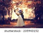 bride and groom in autumn park... | Shutterstock . vector #235943152