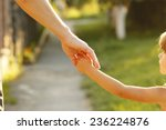 a parent holds the hand of a... | Shutterstock . vector #236224876