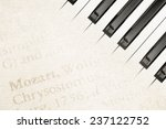 background of mozart text on antique paper with piano keys - stock photo