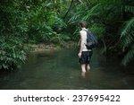 man trekking through tropical... | Shutterstock . vector #237695422