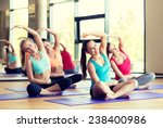 Small photo of fitness, sport, training and lifestyle concept - group of smiling women stretching in gym