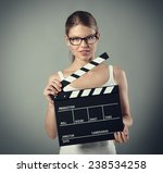 Small photo of Film production and media. Scene tryout. Pretty smiling female with clapperboard over grey background.