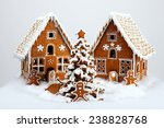 Small photo of The hand-made eatable gingerbread houses and New Year Tree with snow decoration