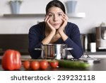 Small photo of Unmotivated attractive young woman preparing the dinner leaning on the hob eyeing the camera with a listless glum expression as she stands in her kitchen in an apron
