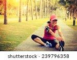 Woman Runner Stretching Legs...