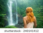 Small photo of Female adventurer looking at waterfall in Bali jungle