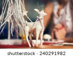 Christmas decoration concept. Vintage toy - christmas deer - with bow on its neck standing on the table with dessert in restaurant. Pastel colors. Retro style. Close up. Indoor shot - stock photo