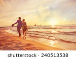 Couple Walking On The Beach At...