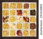 Small photo of Large pasta dried food sampler in square dishes over brown lokta paper background.