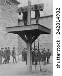 Small photo of Two African American men confined in a Delaware pillory above a whipping post. Spectators to the punishment loiter in the background. 1889.