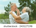 Small photo of Senior couple dancing near lake