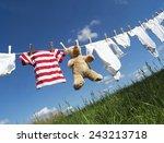 Stock photo baby clothing and a teddybear on a clothesline towards blue sky 243213718
