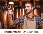 Small photo of Happy brewer. Happy young male brewer in apron holding glass with beer and looking at it with smile while standing in front of metal containers