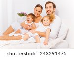 smiling parents on bed with two ... | Shutterstock . vector #243291475