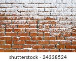 Snow sticking to an old brick wall. - stock photo
