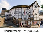 Small photo of LONDON - JULY 1, 2014. People passing by in front of posters advertising plays at The Globe Theater. The theater is a reconstruction of Shakespeare's original globe, opened for performances in 1997.