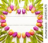 tulips arranged on old wooden... | Shutterstock . vector #243951475