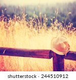 A Hat On A Fence During Sunset...