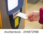 Woman Inserting Ticket Into Machine To Pay For Parking