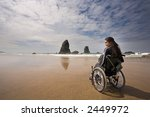 Beautiful young woman in a wheel chair visiting Cannon Beach in Oregon, USA. - stock photo