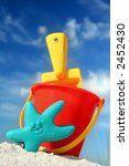 Bucket and spade on tropical beach with blue sky - stock photo