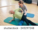 Small photo of Physical therapists assisting senior woman to perform myofascial release technique with a foam roller to inhibit overactive muscles at gym.