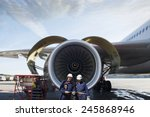 Small photo of airplane mechanics and giant jet engine repair