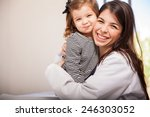 Portrait of a happy Hispanic pediatrician with a little girl as one of her patients, giving her a hug - stock photo