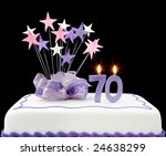 Fancy cake with number 70 candles.  Decorated with ribbons and star-shapes, in pastel tones on black background. - stock photo