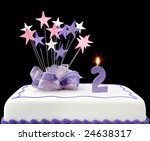 Fancy cake with number 2 candle.  Decorated with ribbons and star-shapes, in pastel tones on black background. - stock photo