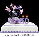 Fancy cake with number 50 candles.  Decorated with ribbons and star-shapes, in pastel tones on black background. - stock photo
