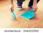 Small photo of cleaning and home concept - close up of male brooming wooden floor with small whisk broom and dustpan