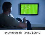 man sitting on couch watching... | Shutterstock . vector #246716542