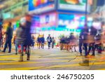 Small photo of Blurred image of people moving in crowded night city street with sopping malls. Hong Kong. Blur effect