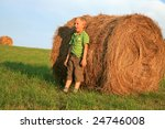 Six-year-old boy wrestling on the meadow. Help with haying,  summer on Polish country. Resting. - stock photo