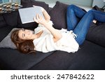 cheerful woman lying on a cosy... | Shutterstock . vector #247842622