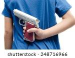 Little boy hinding gun behind...