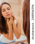 Small photo of Is it acne? Beautiful young woman examining her face while looking at the mirror