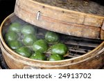 Chinese dumplings in their steamer. FOCUSED AT RIGHT DUMPLINGS - stock photo