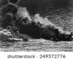 Small photo of Allied tanker torpedoed in Atlantic Ocean by German submarine during World War 2. The ship crumbled amidships under heat of fire as she settled toward bottom of sea. 1942.