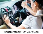 Asian couple driving new car, she is turning on the radio - stock photo
