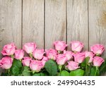 Stock photo valentines day background with pink roses over wooden table top view with copy space 249904435