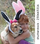 Small photo of little red haired girl with her pet dog dressed up as Easter bunny on an easter egg hunt in meadow of bunnies tail grass