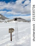 Small photo of Direction sign and ski poles in the snow on country-cross ski slope. Abruzzi, Italy.