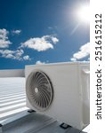 Small photo of White air conditioning unit on a metal industrial roof.