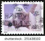 Small photo of UNITED STATES OF AMERICA - CIRCA 2014: forever Christmas stamp printed in USA shows abominable snow monster Bumble staring behind crags of snow; animated TV show Rudolph red-nosed reindeer; circa 2014