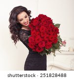 Stock photo fashion interior photo of beautiful smiling woman with dark hair in elegant lace dress holding a 251828488