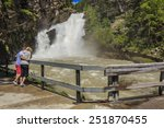 A couple enjoy the fast flowing waterfall at Cameron Falls in Waterton Lakes National Park.