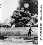 Burning oil tanks and cars left by retreating Dutch in Tandjong, Java. Ca. Feb.-Mar. 1942. World War 2.