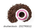 Pink coffee cup inside circle of coffee beans - stock photo